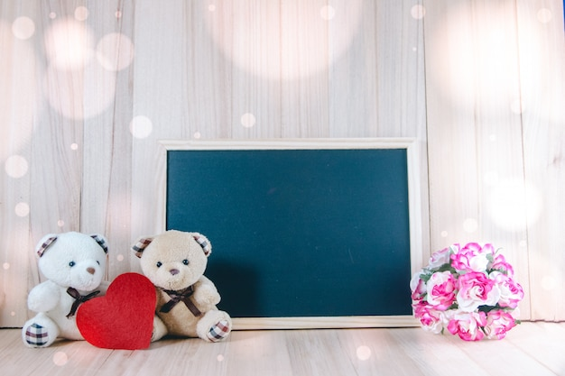 Lovely couple bear sit near blackboard and sweet roses on floor, valentine concept