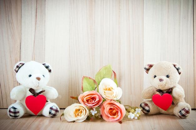 Lovely couple bear sit near sweet roses on floor