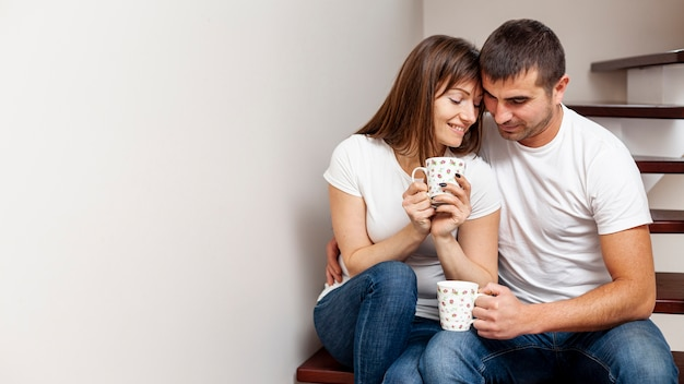 Lovely couple drinking coffee and sitting on stairs