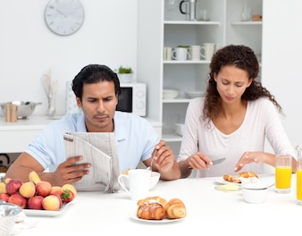 Lovely couple eating cereals and croissants together