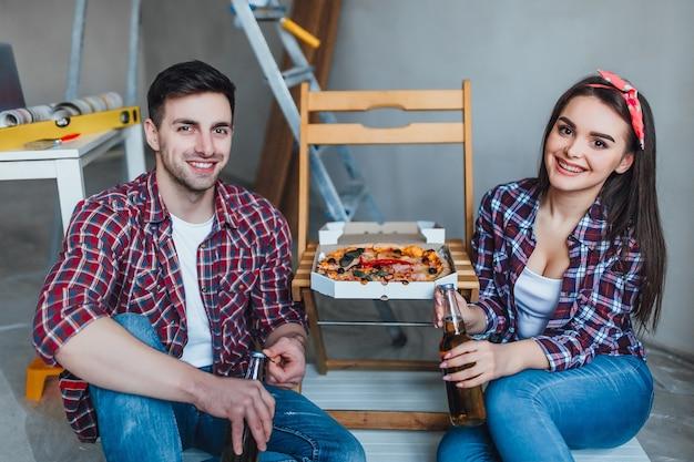 新しいアパートでピザを食べてビールを飲む素敵なカップル