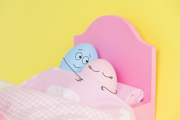 Lovely couple eggs sleeping in an embrace in bed. holding hands.easter holiday concept with cute eggs with funny faces. different emotions and feelings.