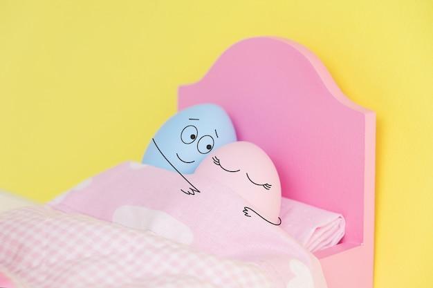 침대에서 포옹에 잠자는 사랑스러운 커플 계란. 손을 잡고. 재미 있은 얼굴을 가진 귀여운 계란 부활절 휴가 개념. 다른 감정과 감정.