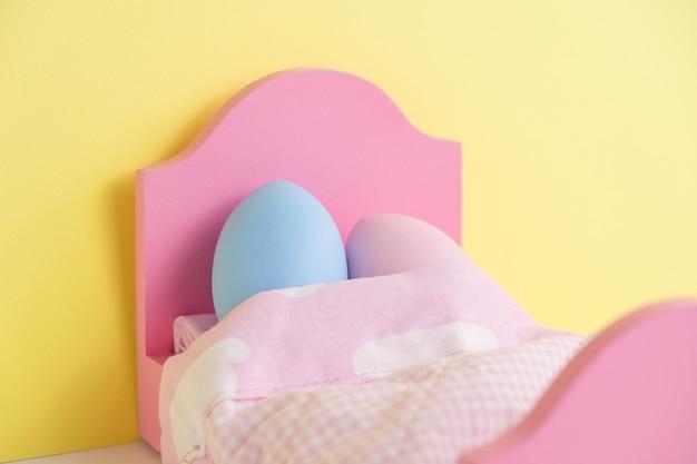 ベッドの抱擁で眠っている素敵なカップルの卵。手をつないで。面白い顔でかわいい卵とイースターの休日のコンセプト。さまざまな感情や感情。