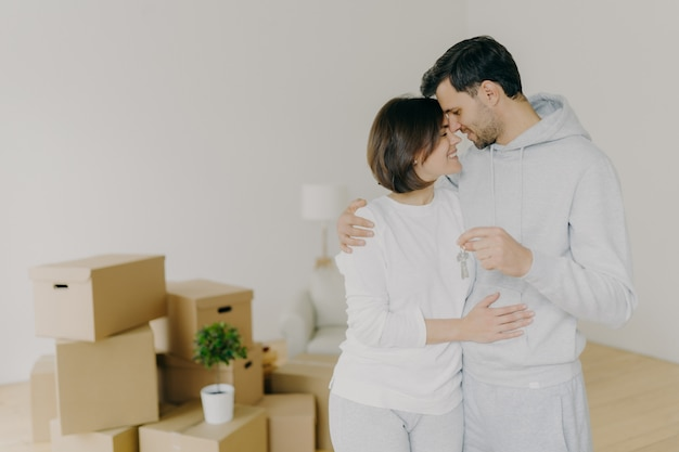 Lovely couple embrace and feel happy, holds keys from new modern first house, move in apartment for living together, pose in empty room with packed carton boxes, feel love to each other. real estate