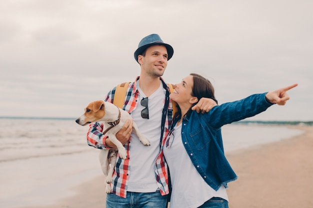 Lovely couple embrace and walk outside on sandy beach, carry favourite dog