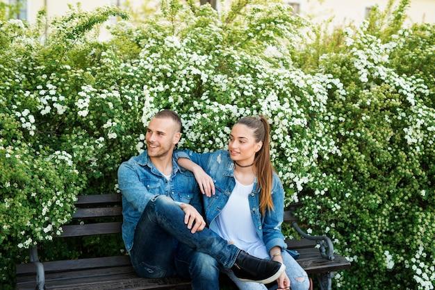 ベンチに座って公園で自由な時間を楽しんでいる素敵なカップル