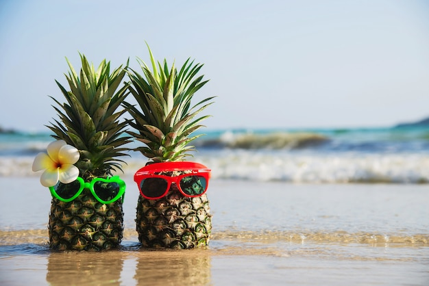 Прекрасная пара свежего ананаса положила солнцезащитные очки на чистый песчаный пляж с морской волной - свежие фрукты с концепцией отдыха на солнце с морским песком