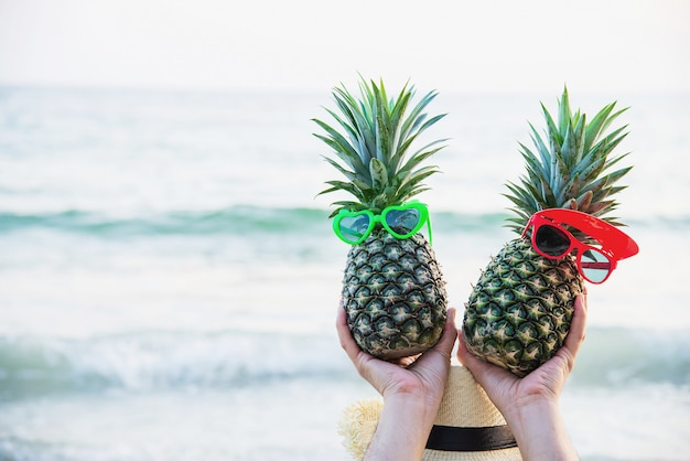 Lovely couple fresh pineapple putting boy and girl glasses in tourist hands with sea wave - happy fun with healthy vacation concept