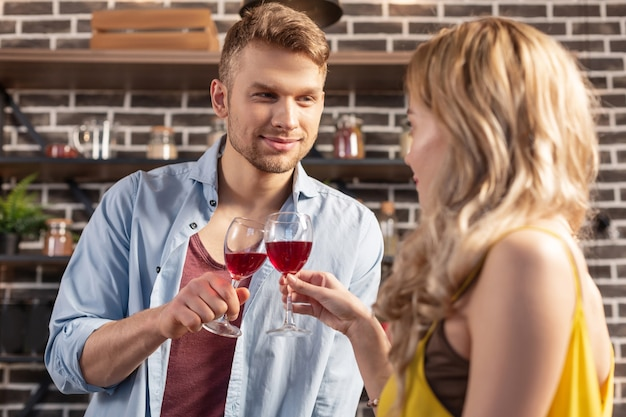 素敵なカップル。一緒に赤ワインを飲みながら金髪の魅力的な妻を見ているハンサムなひげを生やした男