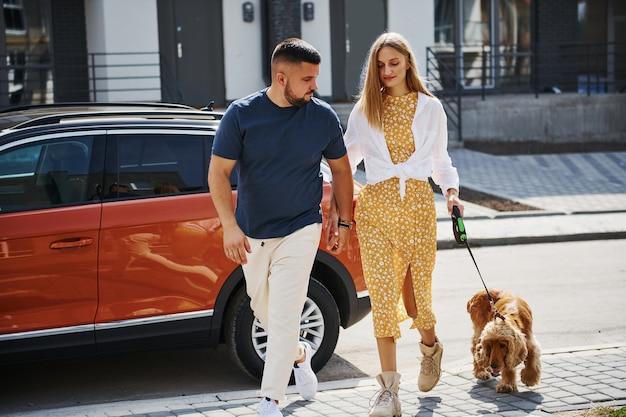 素敵なカップルが車の近くで犬と一緒に屋外で散歩をしています。