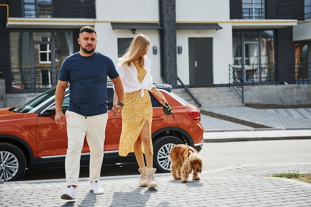 Lovely couple have a walk together with dog outdoors near the car.