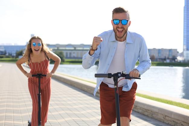 街の遊歩道に沿って電動スクーターを運転して楽しんでいる素敵なカップル。