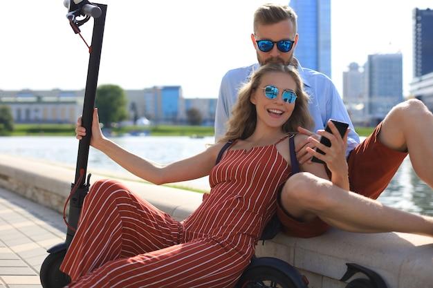 電動スクーターの運転、運転の休憩、川岸に座って、自分撮りを楽しんでいる素敵なカップル、