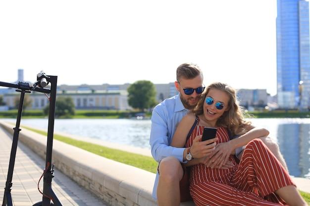 電動スクーターの運転を楽しんだり、運転を休んだり、川岸に座ったり、携帯電話を使ったりする素敵なカップル。
