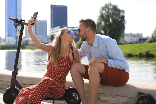 自撮り写真を撮って運転から休憩を取っている電動スクーターを運転して楽しんでいる素敵なカップル