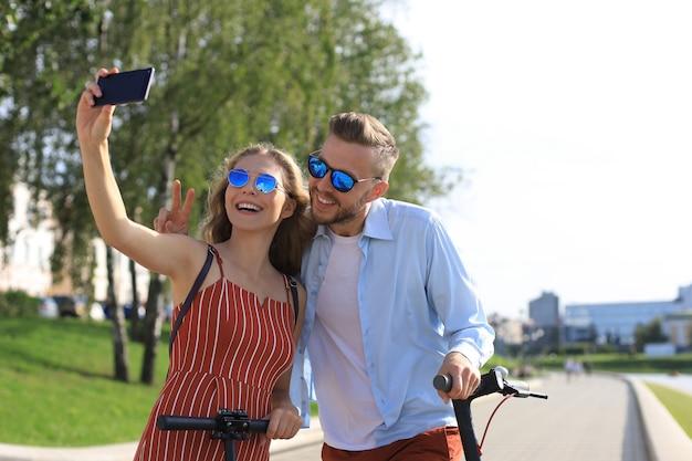 街中を電動スクーターで運転したり、休憩したり、自分撮りを楽しんだりする素敵なカップル。