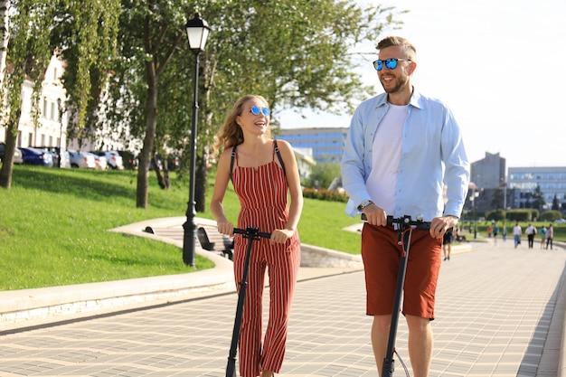 街中を電動スクーターで運転するのを楽しんでいる素敵なカップル。