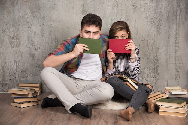 Coppia adorabile che si nasconde dietro i libri e che guarda davanti