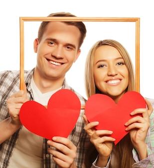フレームと白い背景の上の赤いハートを保持している素敵なカップル。