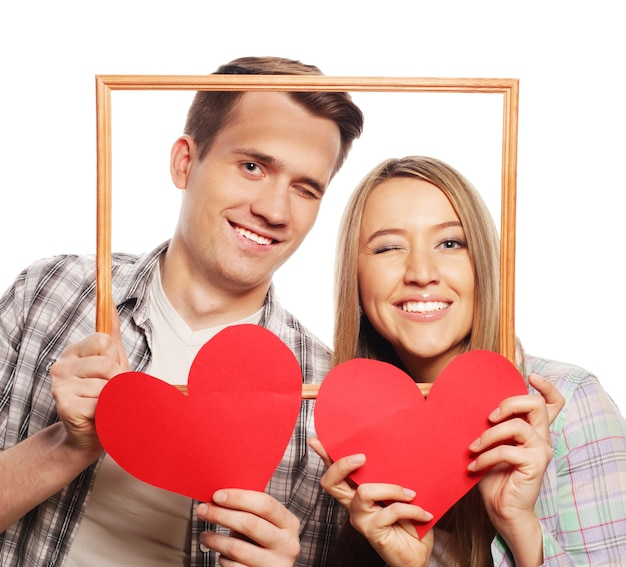 Lovely couple holding frame and red hearts over white background.