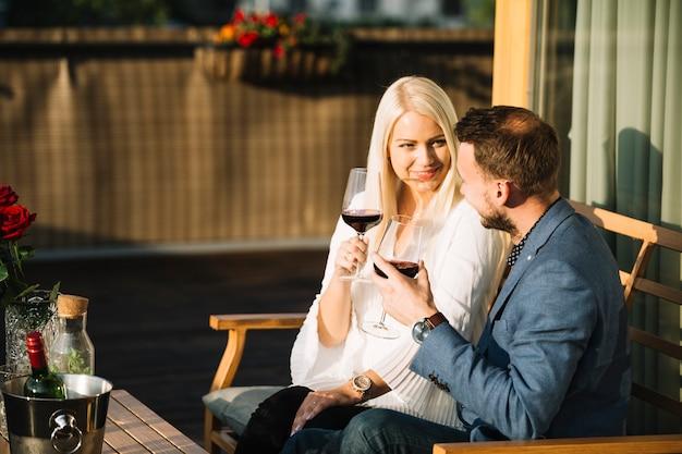 お互いを見て、赤ワインの眼鏡を保持している素敵なカップル