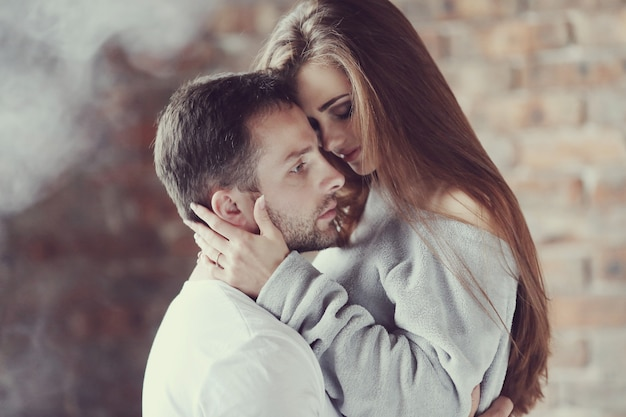 Lovely couple hugging at home