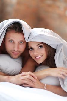 Прекрасная пара в постели под одеялом.