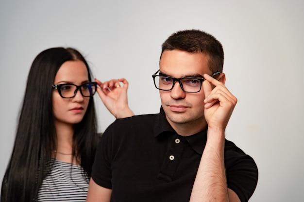 Прекрасная пара в очках. оба трогают очки руками.