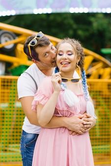 Прекрасная влюбленная пара наслаждается и развлекается в парке развлечений