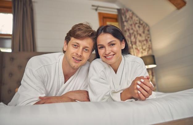사진 카메라에 포즈를 취하는 동안 침실에 누워 흰 가운에 사랑스러운 커플