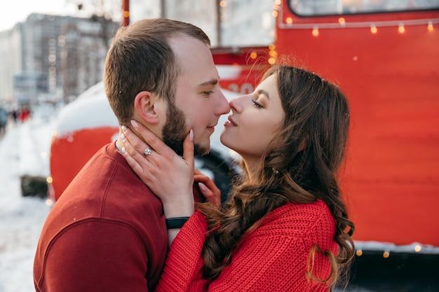 Прекрасная пара поцелуй на фоне красного автобуса. фото высокого качества
