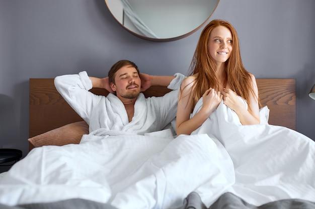 素敵なカップルは親密な後に幸せなベッドに横たわっています