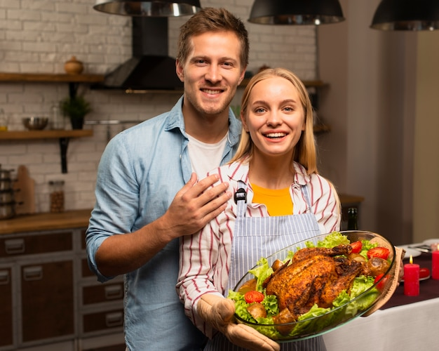 Lovely couple looking at the camera and holding the thanksgiving turkey