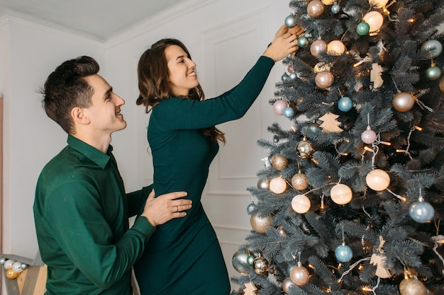 Lovely couple in love decorating a christmas tree