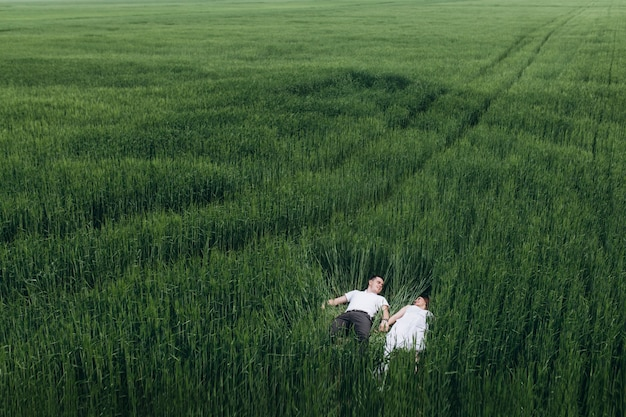 The lovely couple in love lie on the field