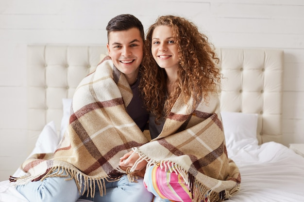 Lovely couple in love warm under plaid in bedroom, embrace each other and have positive smiles on faces, enjoy coziness and togetherness