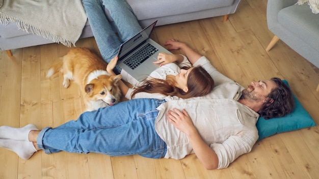 A lovely couple lying on the floor using a laptop, spouses enjoying of each other.