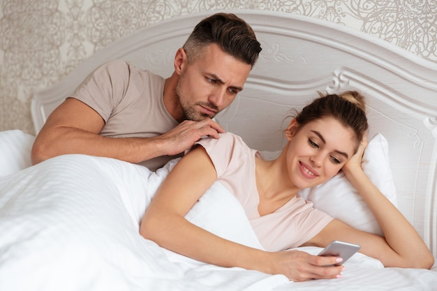 Lovely couple lying together in bed while woman using smartphone