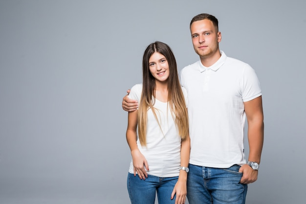 흰색 티셔츠에 사랑스러운 커플 남자와 여자는 회색 배경에 고립 미소
