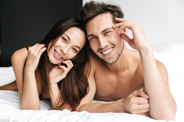 Lovely couple man and woman hugging together, while lying in bed at home or hotel apartment