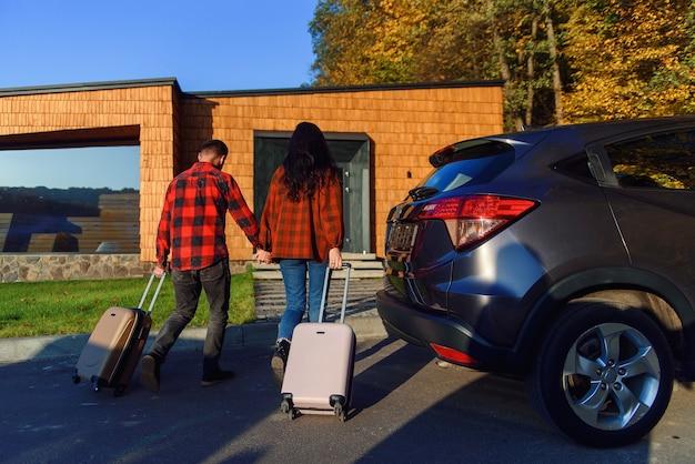 新しい家に引っ越す素敵なカップルは、スーツケースを持って新しい家に入ります。移動時間。