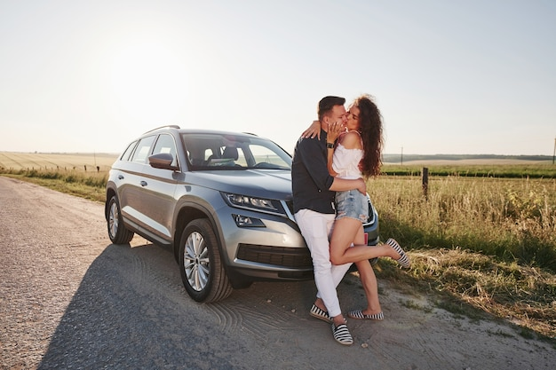 Lovely couple near their new modern car at weekend time.