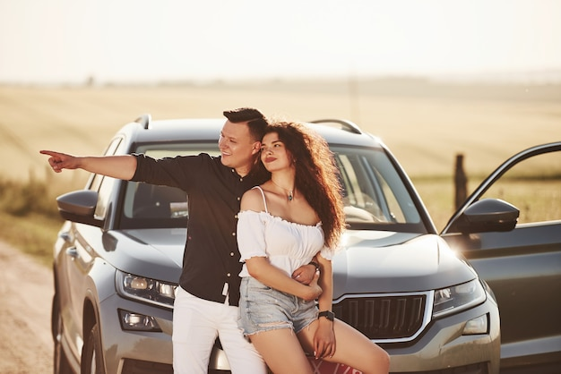 Lovely couple near their new modern car at weekend time