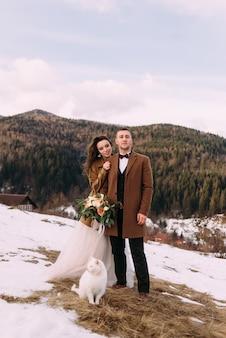 山を背景に素敵な新婚夫婦が立っていて、近くに白猫が座っています。