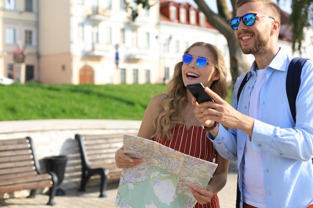 休暇中の素敵なカップルは、方向性のために地図を見ています。