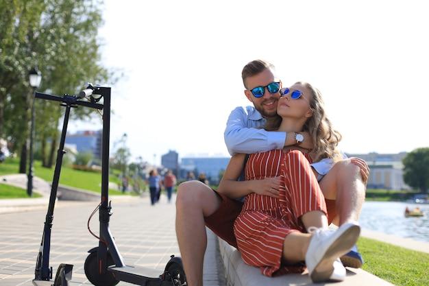 電動スクーターの運転を楽しんだり、運転を休んだり、川岸に座ったりして休暇中の素敵なカップル。