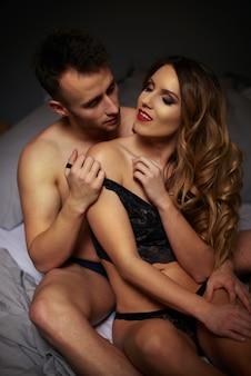 ベッドでポーズをとる素敵なカップル
