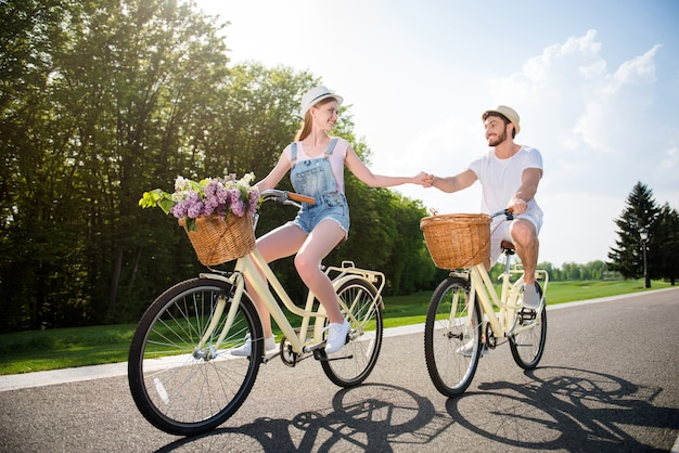 Lovely couple posing together outdoors with bicycles