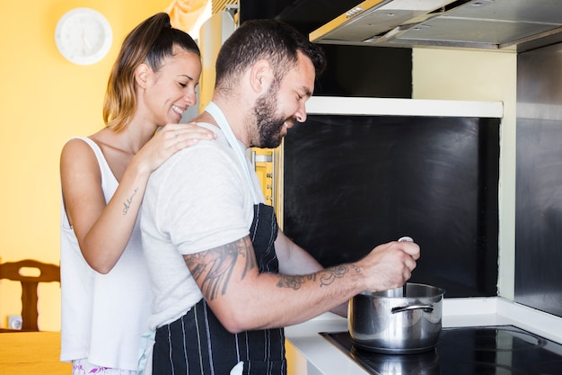 Lovely couple preparing food on induction stove